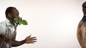 Mięśniowi mężczyzna z różami w ich zębach tanczą i obracają kamera zdjęcie wideo