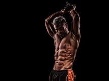 Mięśniowi młodego człowieka udźwigu ciężary na ciemnym tle Zdjęcia Stock