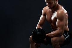 Mięśniowi młodego człowieka udźwigu ciężary na czarnym tle Obraz Royalty Free