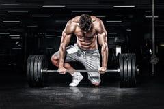 Mięśniowi młodzi sprawność fizyczna sporty obsługują trening z barbell w sprawności fizycznej gym fotografia stock