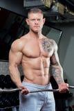 Mięśniowy bez koszuli mężczyzna z niebieskimi oczami i tatuażem w szarości dyszy robić bicepsów kędziorom z EZ kędzioru barem w g Zdjęcia Royalty Free