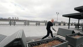 Mięśniowy blondynka młodego człowieka tracer skacze ulicznego akrobatycznego parkour, zwolnione tempo zbiory wideo