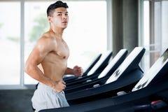 Mięśniowy bodybuilder biegacza faceta ćwiczenia bieg na karuzeli w gym sport sprawności fizycznej młody mężczyzna bez koszuli opr zdjęcie stock