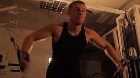 Mięśniowy bodybuilder facet robi ćwiczeniom zbiory