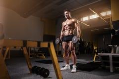 Mięśniowy bodybuilder facet robi ćwiczeniom z dumbbell Fotografia Royalty Free
