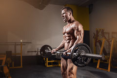 Mięśniowy bodybuilder facet robi ćwiczeniom z dumbbell Obrazy Stock