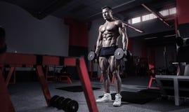 Mięśniowy bodybuilder facet robi ćwiczeniom z dumbbells obrazy stock