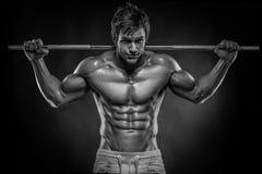Mięśniowy bodybuilder facet robi ćwiczeniom z dumbbells nad bla Fotografia Royalty Free