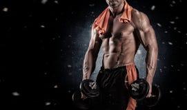 Mięśniowy bodybuilder facet robi ćwiczeniom z dumbbells nad bla Fotografia Stock