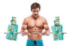 Mięśniowy bodybuilder facet robi ćwiczeniom z prezentami nad białym b zdjęcie stock