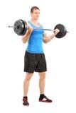 Mięśniowy bodybuilder podnosi barbell Zdjęcia Stock