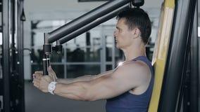 Mięśniowy bodybuilder robi ćwiczenie treningowi w gym dla pierś mięśni Pełnej twarzy strzał zbiory