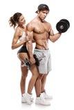 Mięśniowy bodybuilder z kobietą robi ćwiczeniom z dumbbells fotografia royalty free