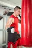 Mięśniowy bokser uderza pięścią torbę Obraz Stock