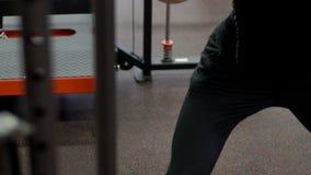 Mięśniowy ciało sportowowie w czarnym sportswear który robi barbell kucnięciom w nowożytnym gym, zbiory