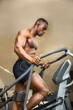 Mięśniowy czarny męski bodybuilder ćwiczy na krok maszynie w gym Fotografia Royalty Free