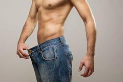Mięśniowy dysponowany mężczyzna jest ubranym dużych cajgi po diety obrazy royalty free