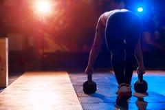 Mięśniowy mężczyzna ćwiczy z czajnika dzwonem w gym Zdjęcie Stock
