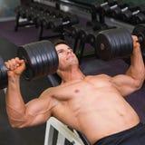Mięśniowy mężczyzna ćwiczy z dumbbells w gym Zdjęcie Stock