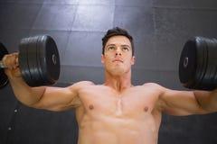 Mięśniowy mężczyzna ćwiczy z dumbbells w gym Obraz Stock