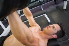 Mięśniowy mężczyzna ćwiczy z dumbbells w gym Fotografia Stock