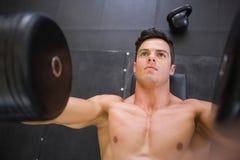 Mięśniowy mężczyzna ćwiczy z dumbbells w gym Obrazy Stock