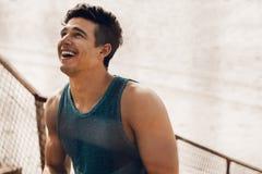 Mięśniowy mężczyzna bierze przerwę po treningu i śmiać się Zdjęcie Stock