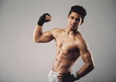 Mięśniowy mężczyzna ciągnie jego bicep pokazywać daleko Obrazy Royalty Free