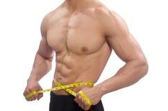 Mięśniowy mężczyzna mierzy jego mięśnie Obrazy Royalty Free