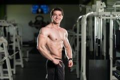 Mięśniowy mężczyzna napina mięśnie w gym Zdjęcie Stock