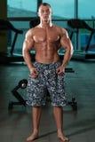 Mięśniowy mężczyzna napina mięśnie w gym Zdjęcie Royalty Free