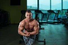 Mięśniowy mężczyzna napina mięśnie w gym Obrazy Stock