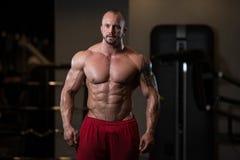Mięśniowy mężczyzna napina mięśnie w gym Fotografia Stock