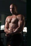 Mięśniowy mężczyzna napina mięśnie w gym Obraz Stock
