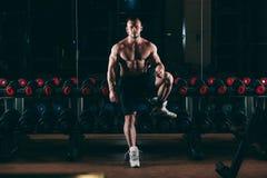 Mięśniowy mężczyzna out w gym stoi blisko dumbbells, silny męski nagi półpostaci abs Zdjęcie Stock
