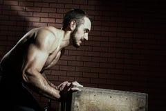 Mięśniowy mężczyzna pcha drewnianego pudełko Obraz Royalty Free
