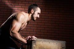 Mięśniowy mężczyzna pcha drewnianego pudełko Obraz Stock