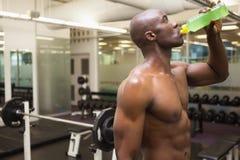 Mięśniowy mężczyzna pije energetycznego napój w gym Zdjęcia Stock