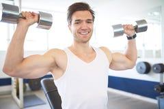 Mięśniowy mężczyzna Podnosi Dwa Dumbbells w Gym zdjęcie royalty free