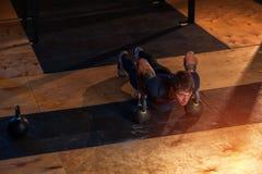Mięśniowy mężczyzna podnosi z czajnika dzwonem robić pcha Obrazy Royalty Free