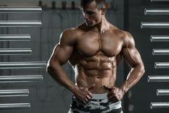 Mięśniowy mężczyzna pokazuje mięśnie, pozuje w gym Silny męski nagi półpostaci abs, pracujący out Zdjęcie Stock