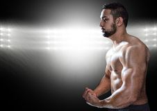 Mięśniowy mężczyzna pozuje przeciw czerń iluminującemu tłu Fotografia Stock