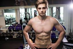 Mięśniowy mężczyzna pracujący w gym robi ćwiczeniom przy triceps out, silny męski nagi półpostaci abs przydatność Zdjęcia Royalty Free