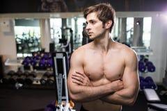 Mięśniowy mężczyzna pracujący w gym robi ćwiczeniom przy triceps out, silny męski nagi półpostaci abs przydatność Zdjęcie Royalty Free