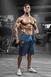 Mięśniowy mężczyzna pracujący w gym robi ćwiczeniom z barbell out, silny męski nagi półpostaci abs Zdjęcie Royalty Free