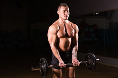 Mięśniowy mężczyzna pracujący w gym robi ćwiczeniom z barbell out, silny męski nagi półpostaci abs Fotografia Stock