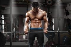 Mięśniowy mężczyzna pracujący w gym robi ćwiczeniom z barbell przy bicepsami out, silny męski nagi półpostaci abs Zdjęcia Royalty Free