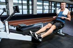 Mięśniowy mężczyzna używa wioślarską maszynę Fotografia Royalty Free