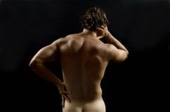 Mięśniowy mężczyzna z bólem pleców, czarny blackground Obraz Stock