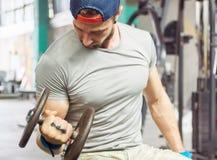 Mięśniowy męski bodybuilder w popielatej koszulki i palmy ochronie gr Zdjęcie Stock
